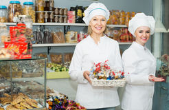 Smiling females staff offering sweets. In local confectionery Stock Photography