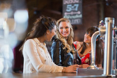 Smiling females standing by bar counter. In pub Royalty Free Stock Photography