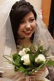 Smiling fiancee with flowers in the hands royalty free stock photography