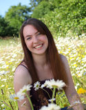 Smiling in a field of daisies. Pretty teen girl smiles while surrounded by daisies Royalty Free Stock Photos