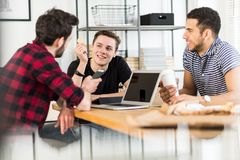 Smiling financier holding gold coin while talking to his friends. About BitCoin royalty free stock images