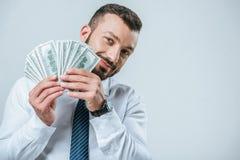 Smiling financier showing dollars isolated. On grey stock image