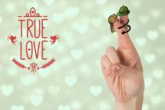 Smiling finger couple with true love message. Against digitally generated hearts background Stock Image