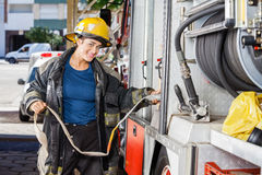 Smiling Firefighter Adjusting Water Hose In Truck Royalty Free Stock Images