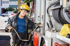 Smiling Firefighter Adjusting Water Hose In Truck. Portrait of smiling female firefighter adjusting water hose in truck at fire station royalty free stock images
