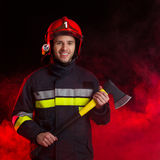 Smiling firefighter holding axe. Stock Images