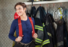 Smiling Firefighter Standing At Fire Station. Smiling female firefighter looking away while standing at fire station stock photos