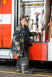 Smiling Firefighter Standing By Truck At Fire. Full length portrait of smiling female firefighter standing by truck at fire station stock photo