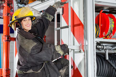 Smiling Firefighter Standing On Truck At Fire Stock Images