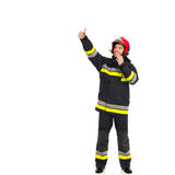 Smiling fireman directing. Smiling fireman with walkie talkie directing and showing thumb up. Full length studio shot isolated on white Royalty Free Stock Photos