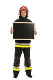 Smiling fireman holding blackboard. Royalty Free Stock Photos