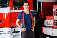 Smiling Fireman Standing Against Trucks Royalty Free Stock Photos