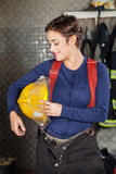 Smiling Firewoman Holding Helmet At Fire Station Stock Images