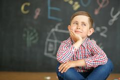 A smiling first grader sits on the background of a school board. royalty free stock images