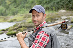 Smiling fisherman. Closeup of fly-fisherman holding fishing rod in river Royalty Free Stock Photo