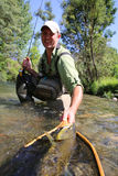 Smiling fisherman with big trout Royalty Free Stock Images