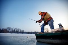 Smiling fisherman catch fish on the frozen river in winter. Smiling elderly fisherman catch fish on the frozen river in winter Stock Photo