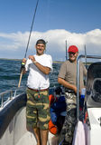 Smiling fishermen. Two smiling fishermen with their fishing rods, on the sea (ocean) on a motorboat Royalty Free Stock Photos