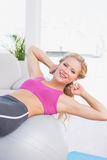 Smiling fit blonde doing sit ups with exercise ball Royalty Free Stock Photos