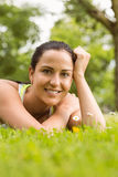 Smiling fit brunette lying on grass and looking at camera Royalty Free Stock Photos