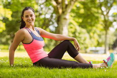 Smiling fit brunette relaxing on the grass Stock Photo
