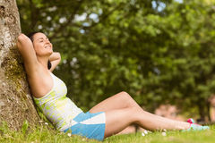 Smiling fit brunette sitting and relaxing against a tree Royalty Free Stock Image