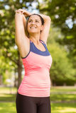 Smiling fit brunette stretching her arms Stock Photo