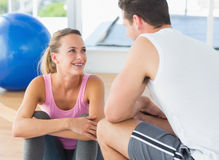 Smiling fit couple chatting in exercise room. Smiling young fit couple chatting in a bright exercise room Royalty Free Stock Photos