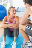 Smiling fit couple chatting in exercise room. Smiling young fit couple chatting in a bright exercise room Stock Image