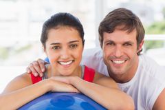 Smiling fit couple with exercise ball at gym. Closeup portrait of a smiling fit couple with exercise ball at a bright gym Royalty Free Stock Photo