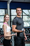 Smiling fit couple lifting dumbbells. At gym Stock Image