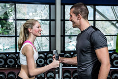Smiling fit couple lifting dumbbells. At gym Royalty Free Stock Photography
