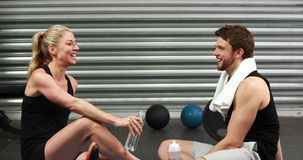 Smiling fit couple sitting on mat talking stock footage