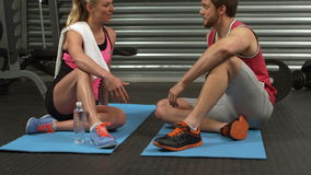 Smiling fit couple sitting on mat talking at the gym stock video footage