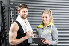 Smiling fit couple taking notes. At crossfit gym Stock Photography