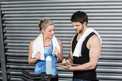 Smiling fit couple taking notes. At crossfit gym Stock Photos