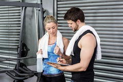 Smiling fit couple taking notes. At crossfit gym Royalty Free Stock Photography