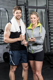 Smiling fit couple taking notes. At crossfit gym Royalty Free Stock Photos