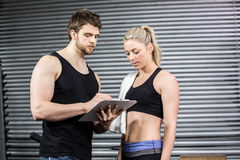 Smiling fit couple taking notes. At crossfit gym Stock Images