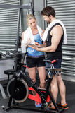 Smiling fit couple taking notes. At crossfit gym Royalty Free Stock Photo