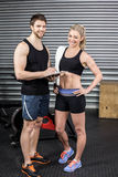 Smiling fit couple taking notes. At crossfit gym Royalty Free Stock Image