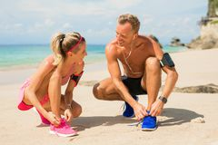Couple tying trainers before training on the beach. Smiling and fit couple tying trainers before training on the beach Royalty Free Stock Images
