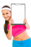 Smiling fit girl looking from blank clipboard Royalty Free Stock Images