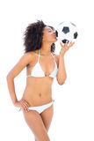 Smiling fit girl in white bikini kissing football Stock Photos
