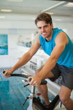 Smiling fit man on the spin bike Royalty Free Stock Image