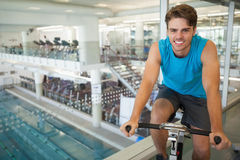 Smiling fit man on the spin bike Stock Photos