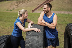 Smiling fit man and woman interacting with each other during obstacle course. Smiling fit men and women interacting with each other during obstacle course in royalty free stock photos