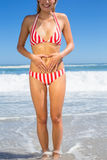 Smiling fit woman in bikini on the beach touching her stomach Stock Photography