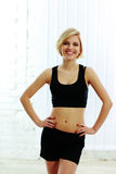 Smiling fit woman in black sports bra Stock Photo