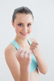 Smiling fit woman clenching fists against wall Stock Image